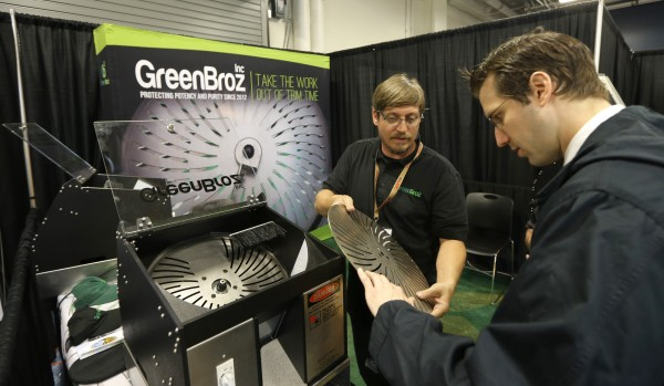 Cullen Raichart, center, CEO of GreenBroz, Inc., shows a prospective customer one of the blades of a mechanical pot trimming machine on display at CannaCon.   (AP Photo/Ted S. Warren)