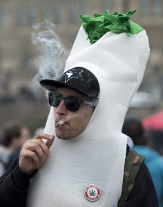 A man dressed in a marijuana joint costume smokes a joint during a 4/20 protest on Parliament Hill, Monday, April 20, 2015 in Ottawa, Ontario. (Adrian Wyld/The Canadian Press via AP)